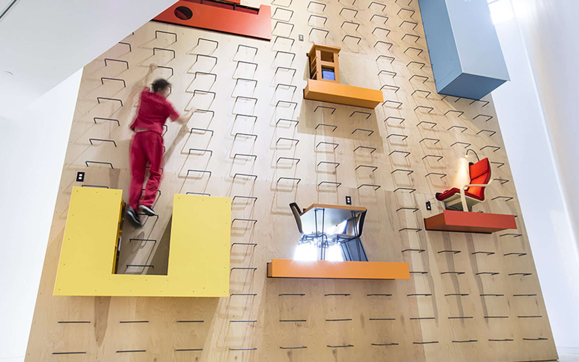 Person scales a large wall installation