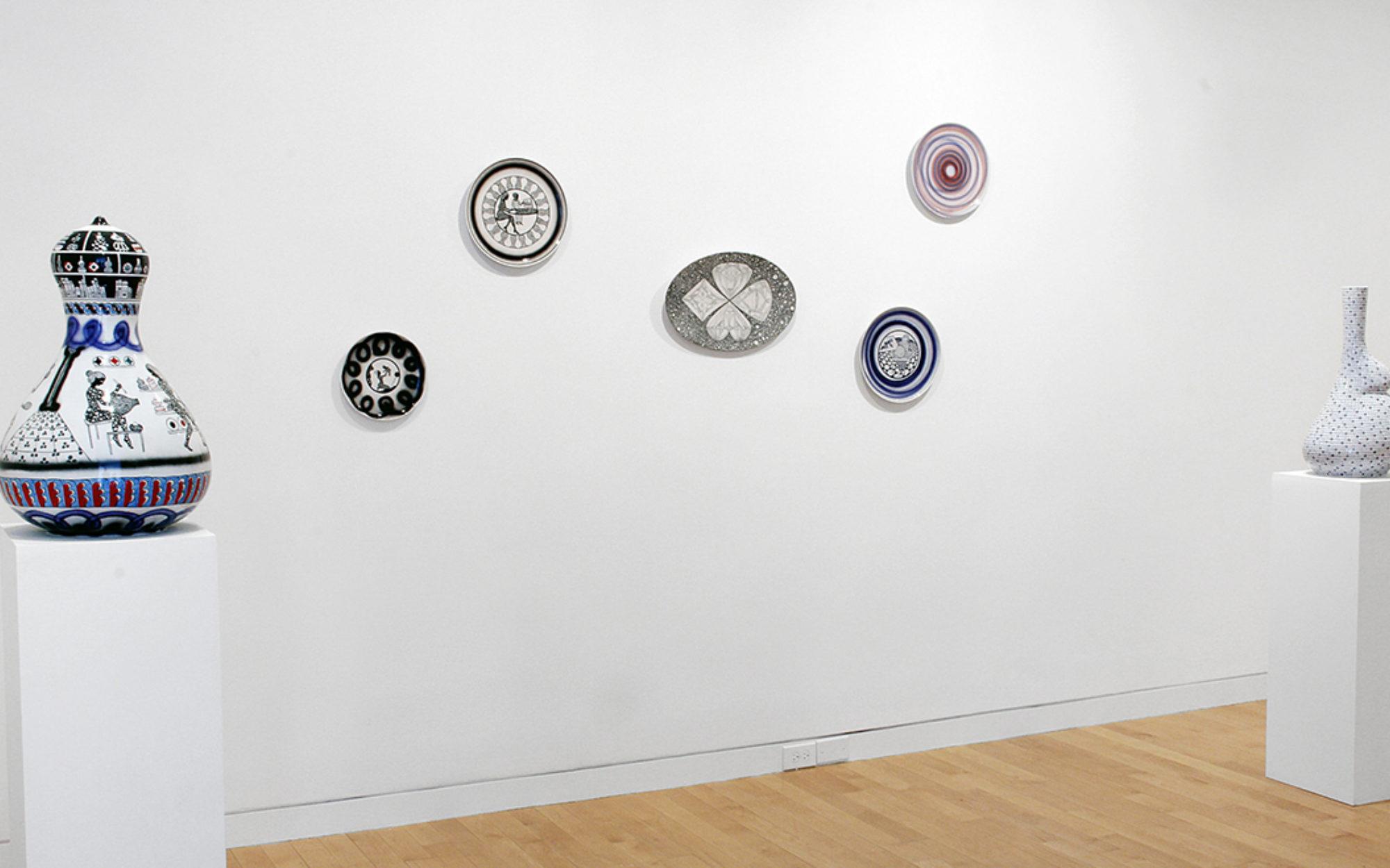 Ceramic vases sit on white pillars, ceramic plates hang on gallery walls