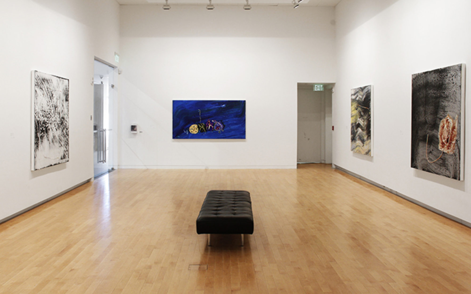 Jack Whitten's artwork hangs on the gallery walls, small black bench sits in the middle of the room