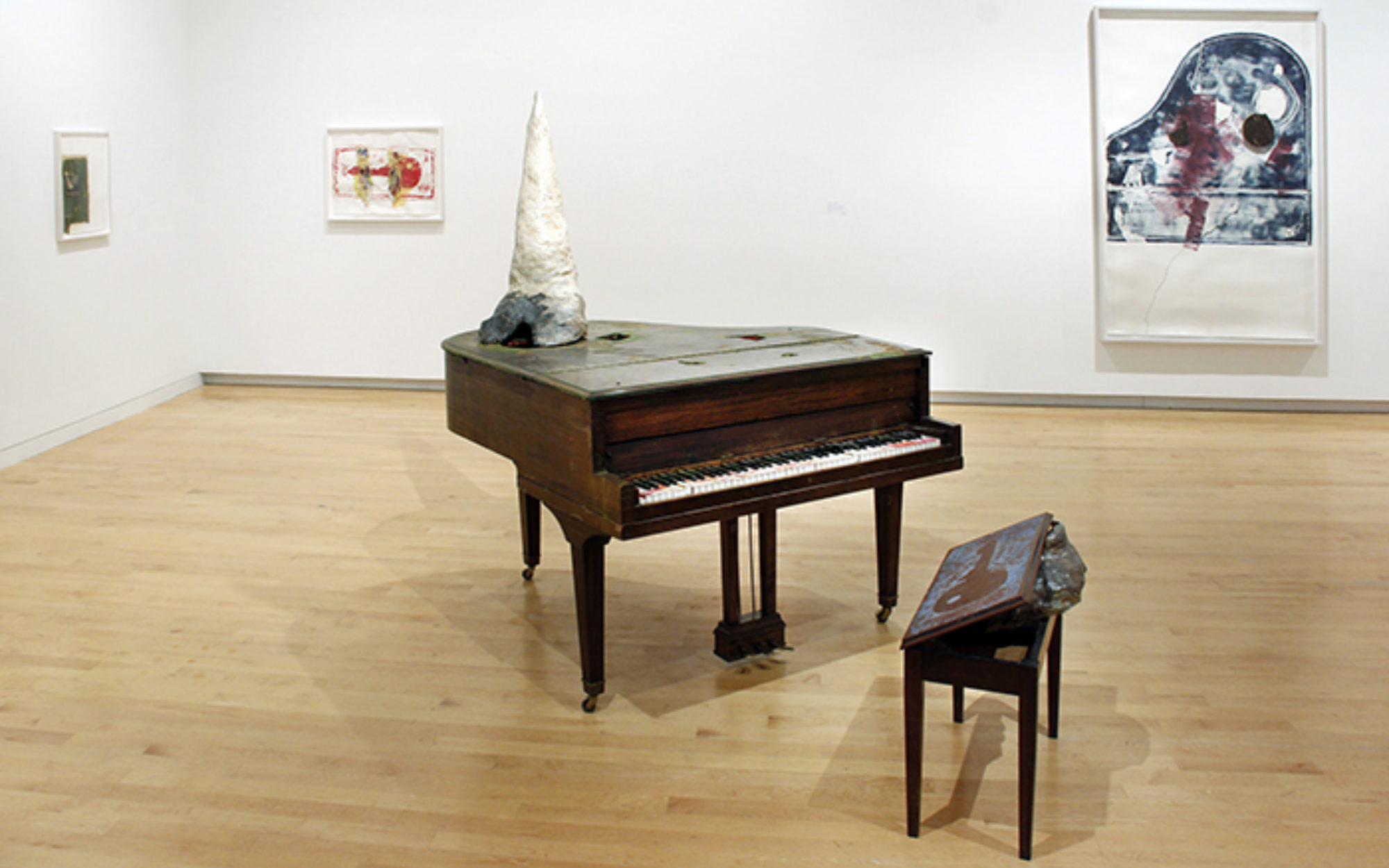 Piano sits in the center of room with a unicorn horn mounted on top