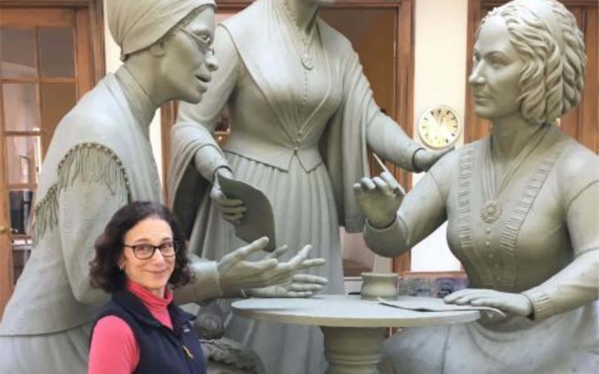 A woman standing in front of a large scale sculpture of three women.