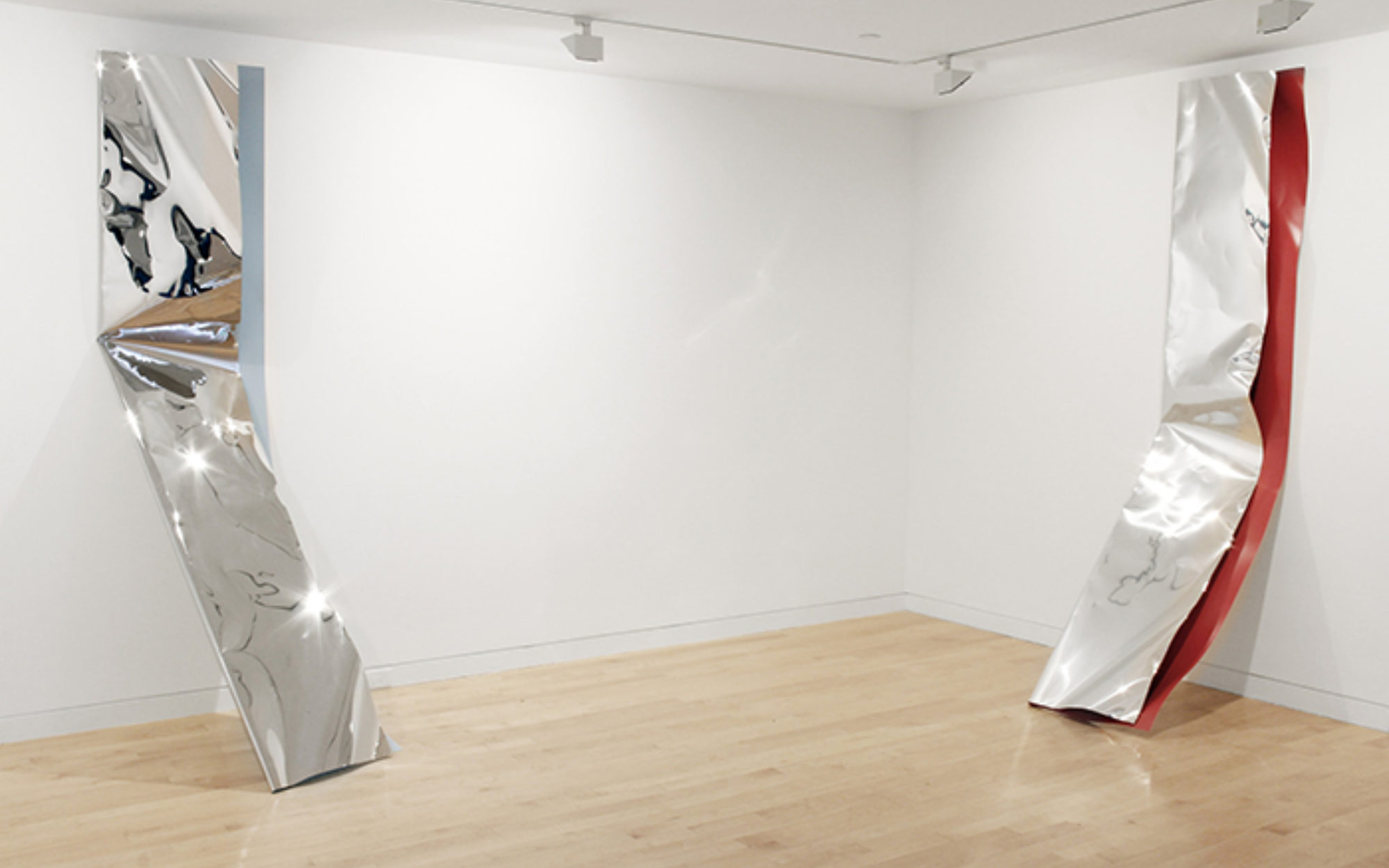 Two crushed metal pieces lean against the gallery walls