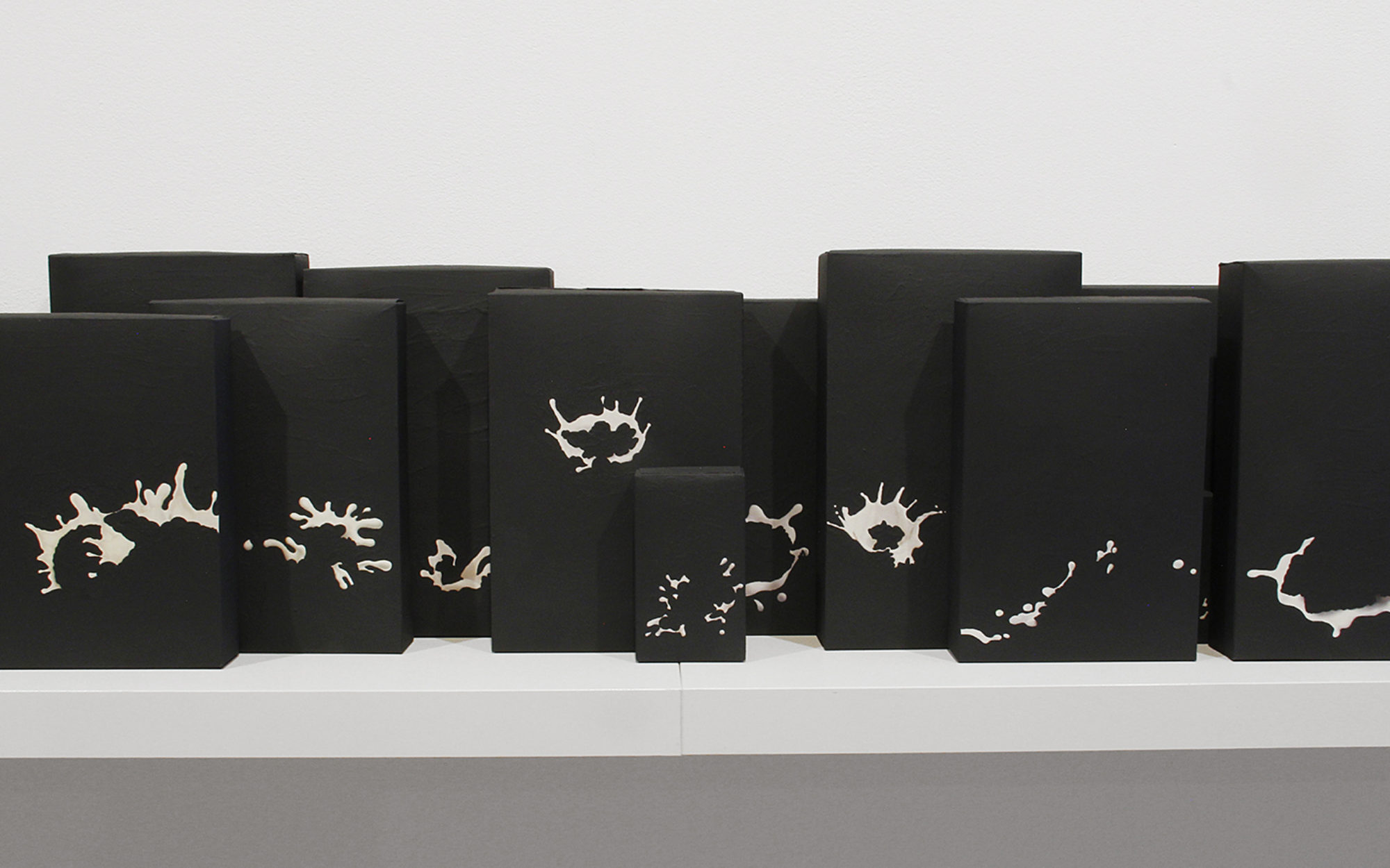 Small black sculptural works on a white shelf