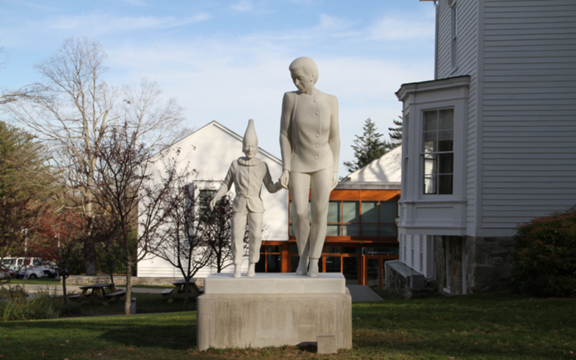 Small sculptural figures walk hand and hand with Museum in the background