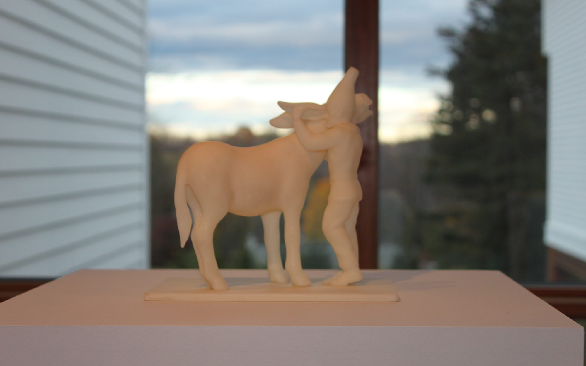 Small figurine of a figure hugging a horse