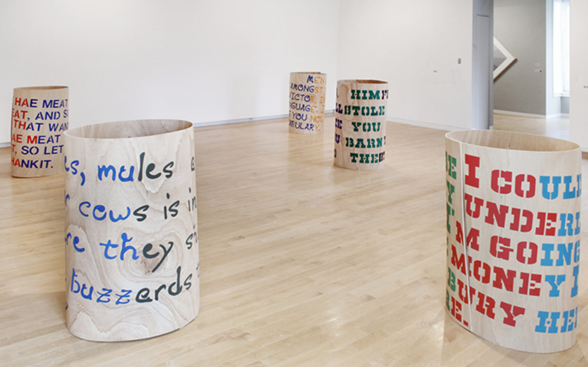 Five circular forms with lettering on them sit on the gallery floor