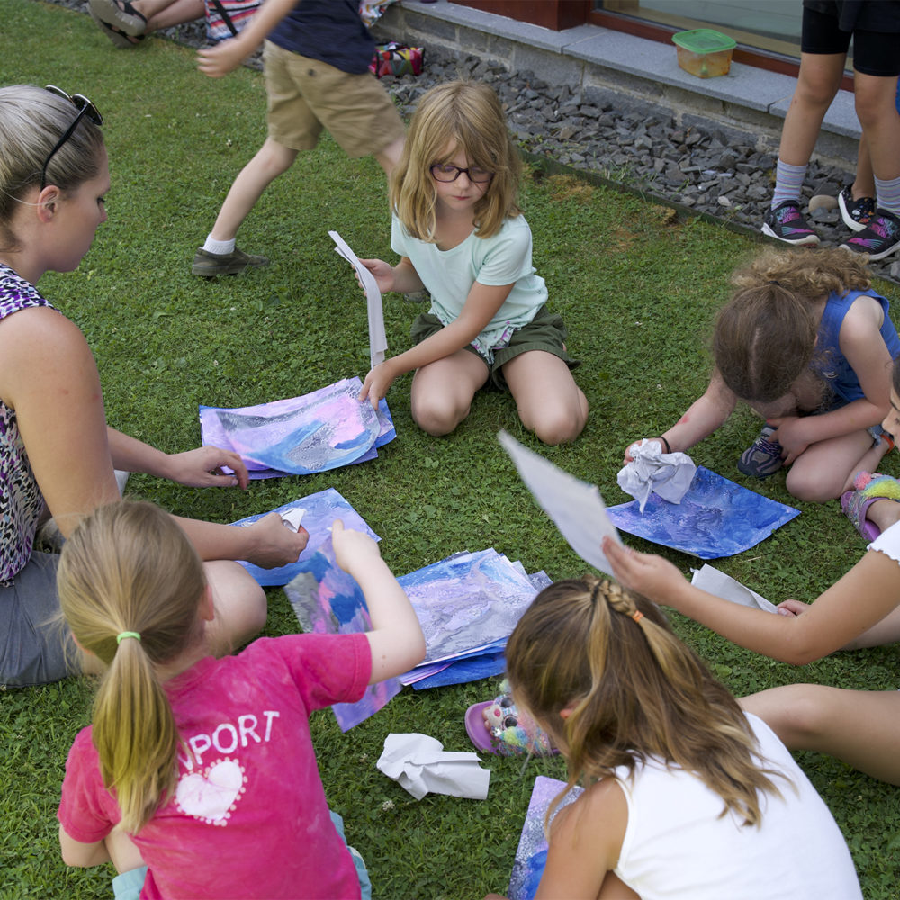 Children work on art projects outside