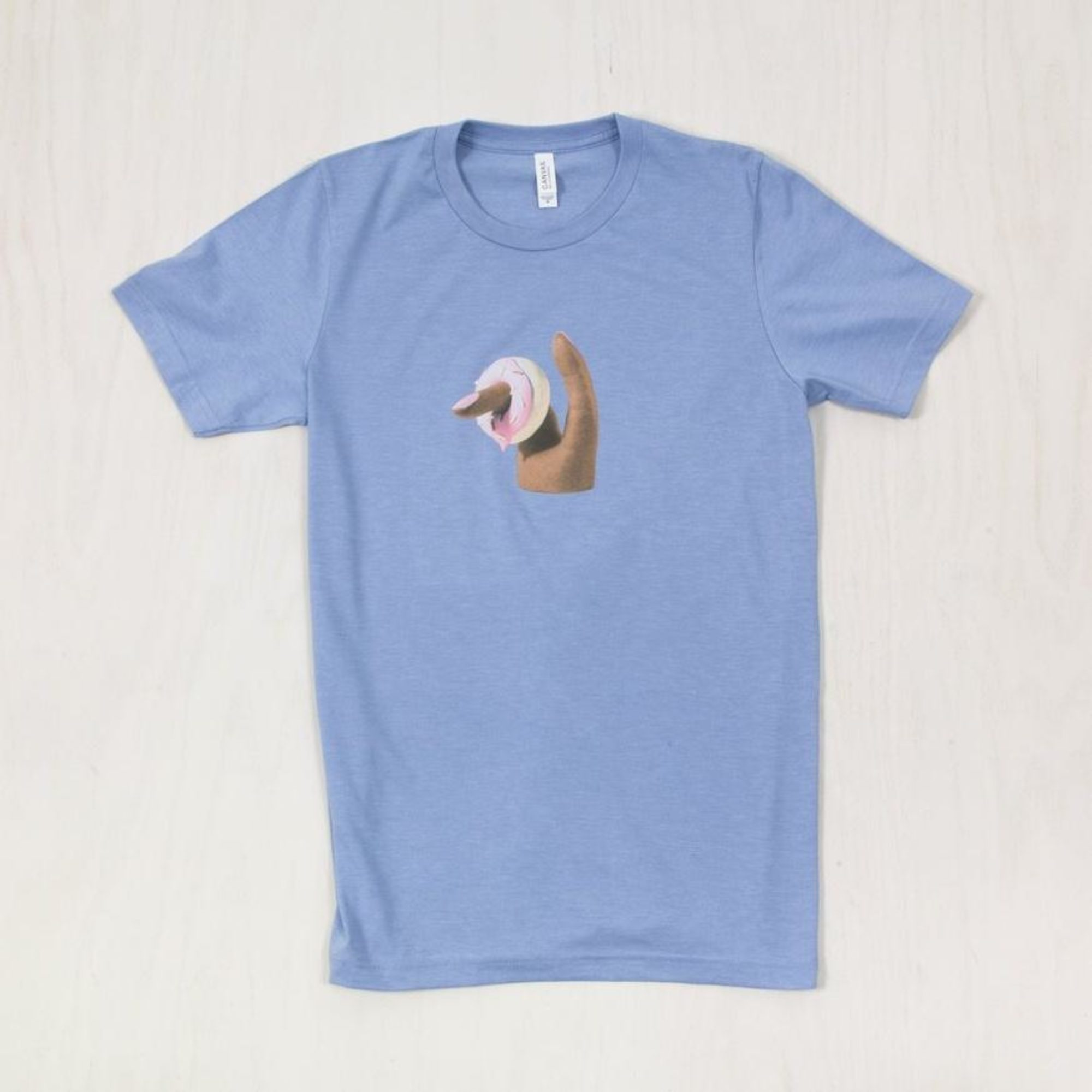 Light blue t-shirt featuring finger inserted into a pink frosted donut
