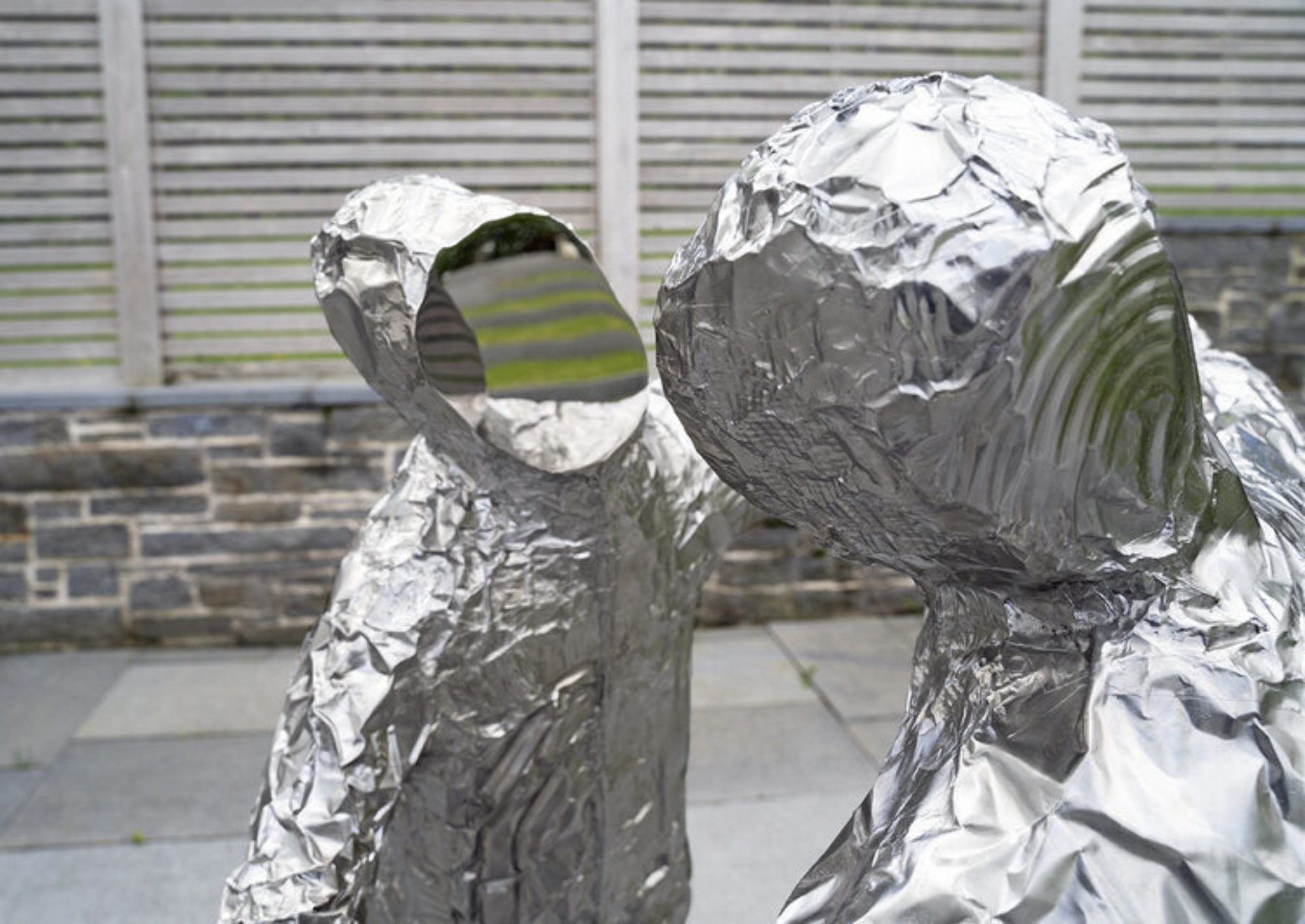 Close up of two figures with mirrored faces