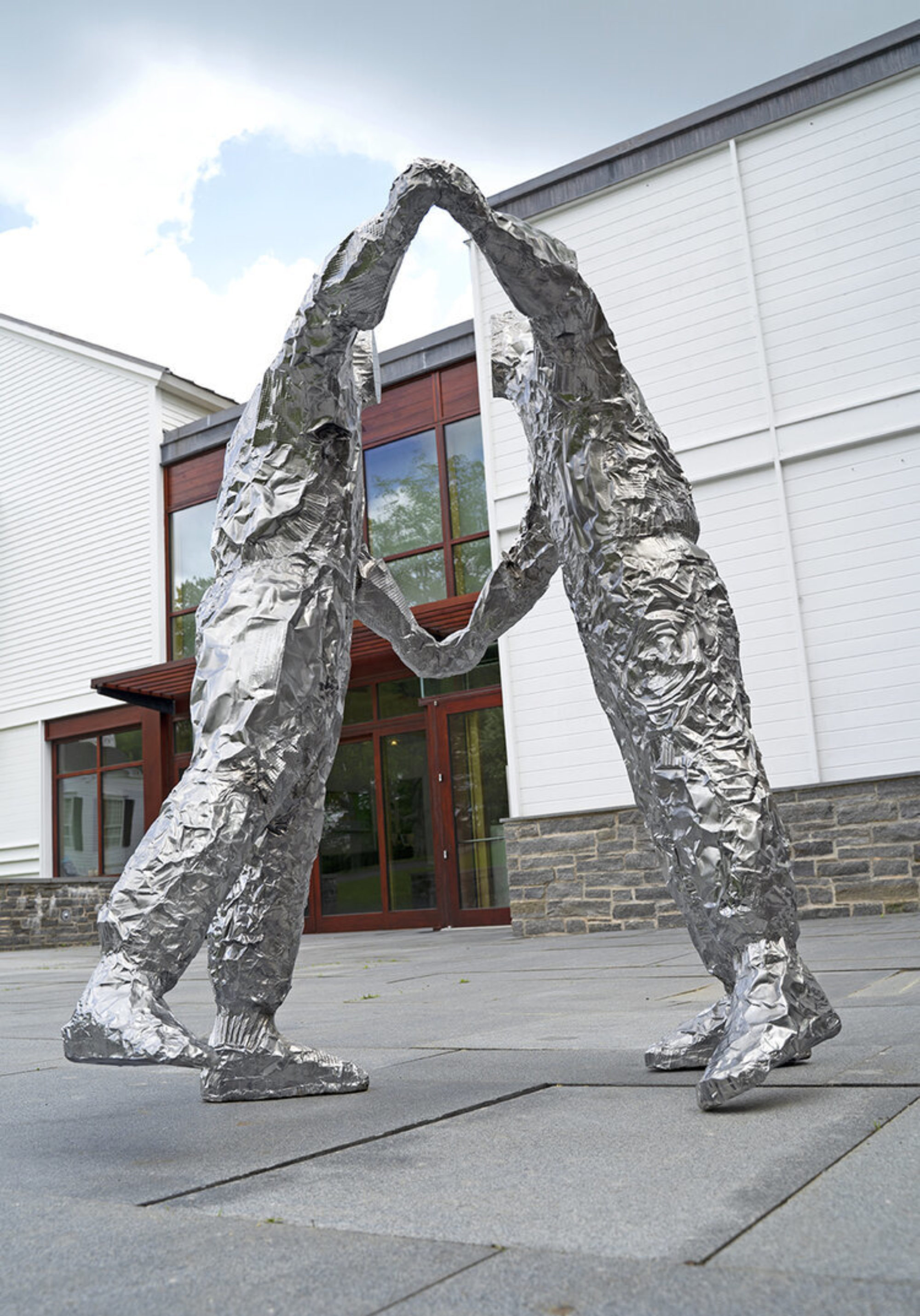 Two figures made out of crumpled baking pans cast in polished stainless steel with a large white building in the background