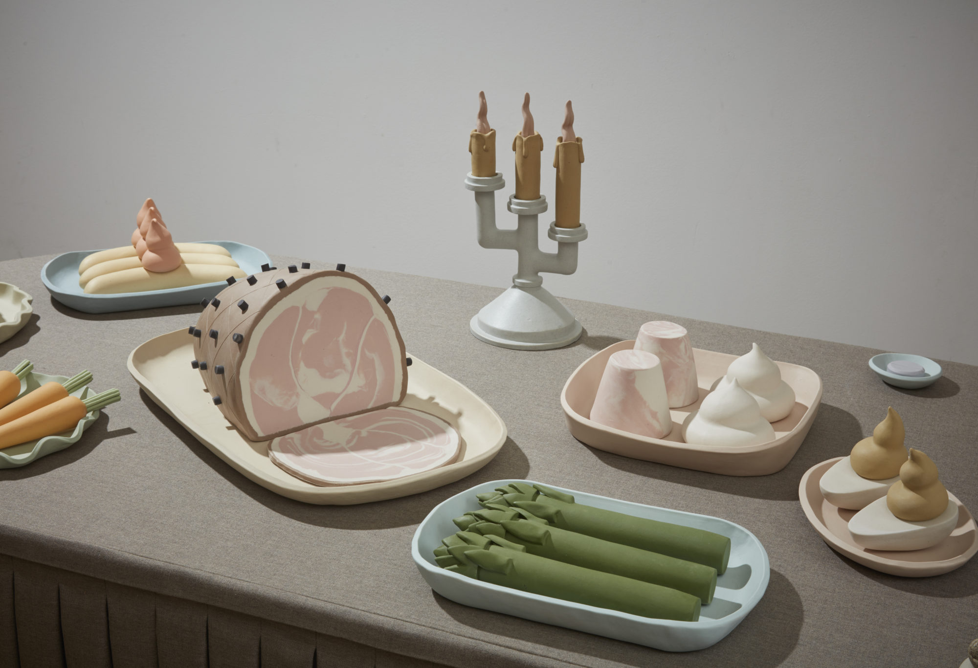 Small sculptural food items arranged on a gray table