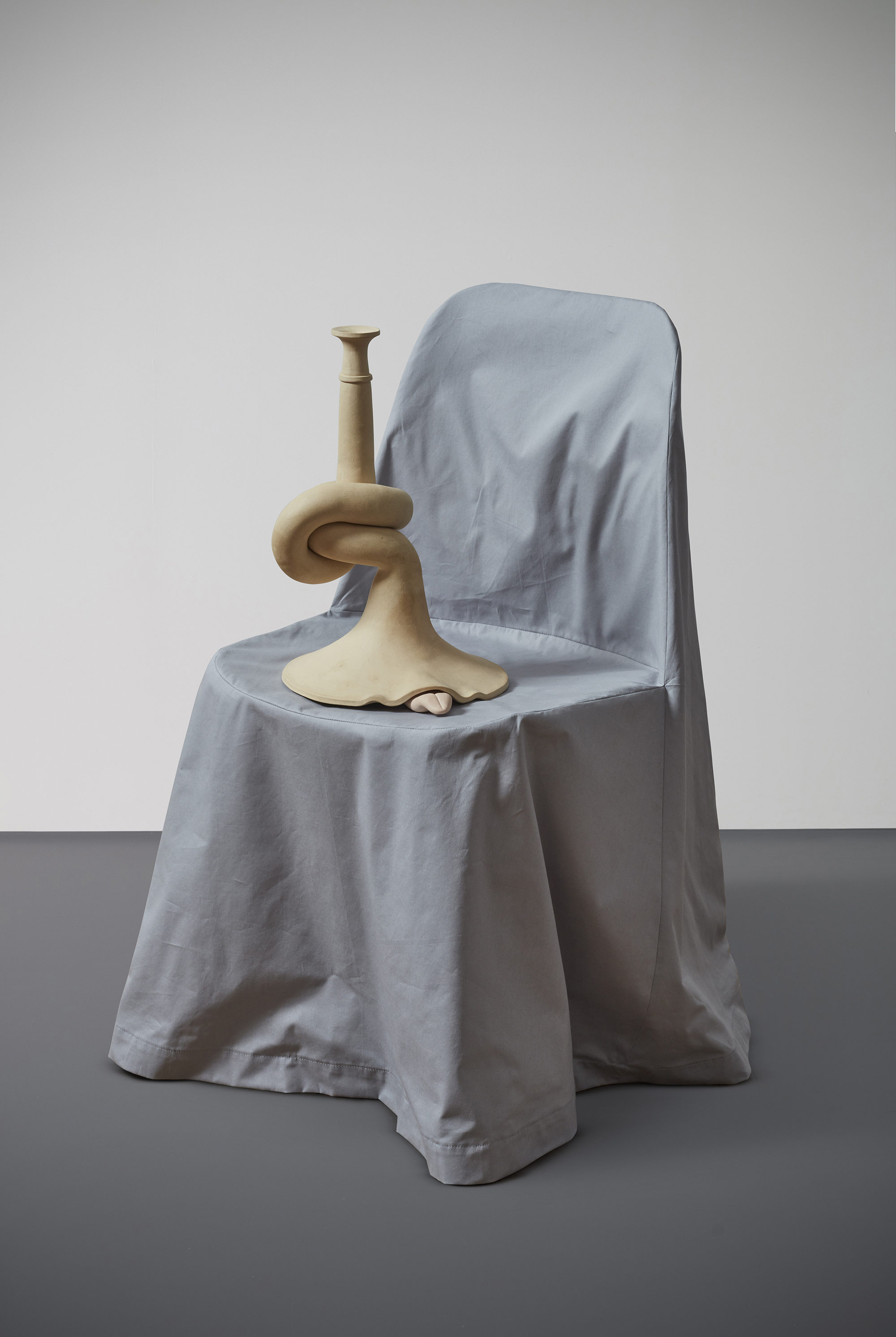 Small sculptural object on a gray chair