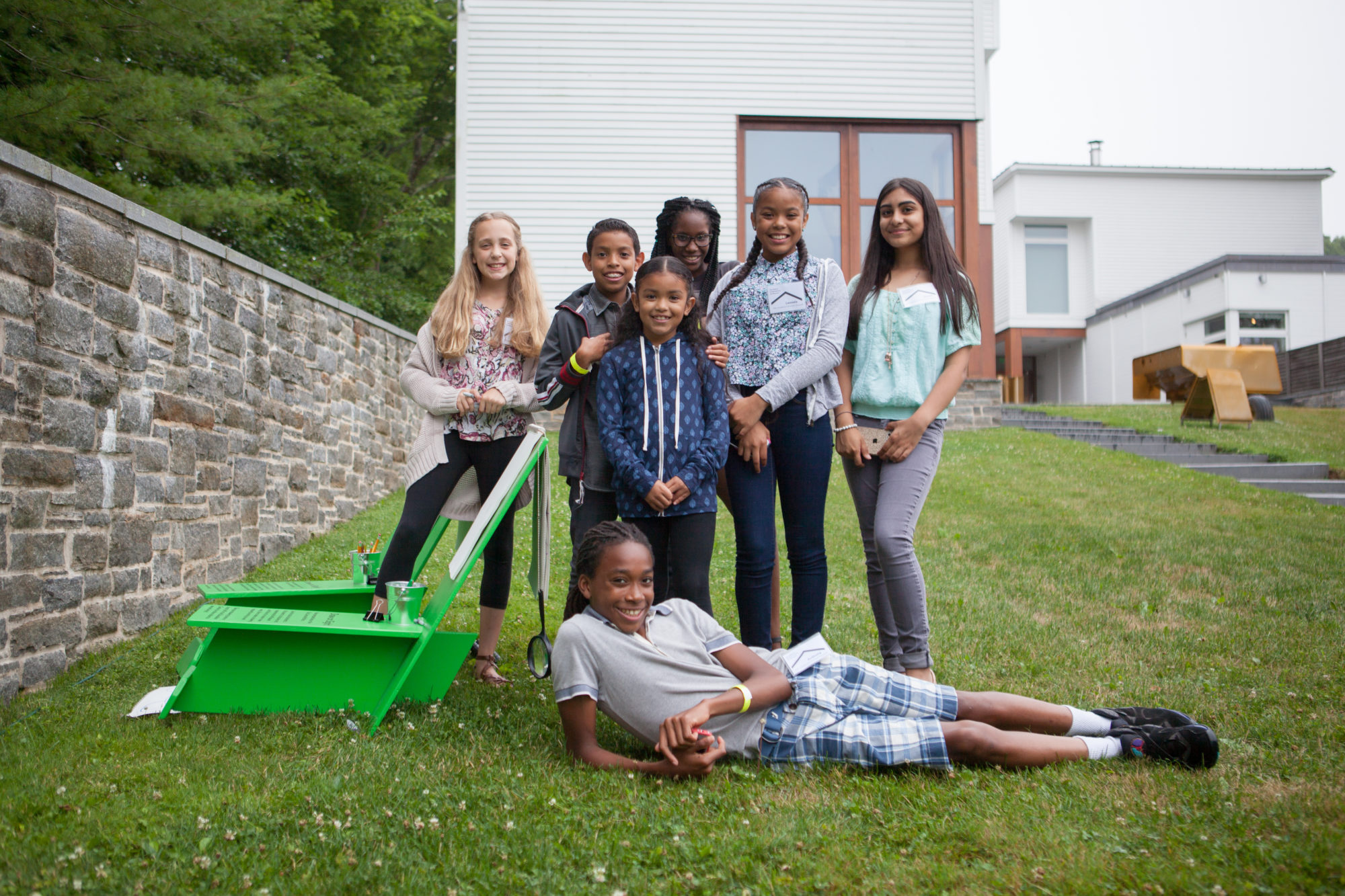 A group of students in the Museum's Sculpture Garden by a green lawn chair.