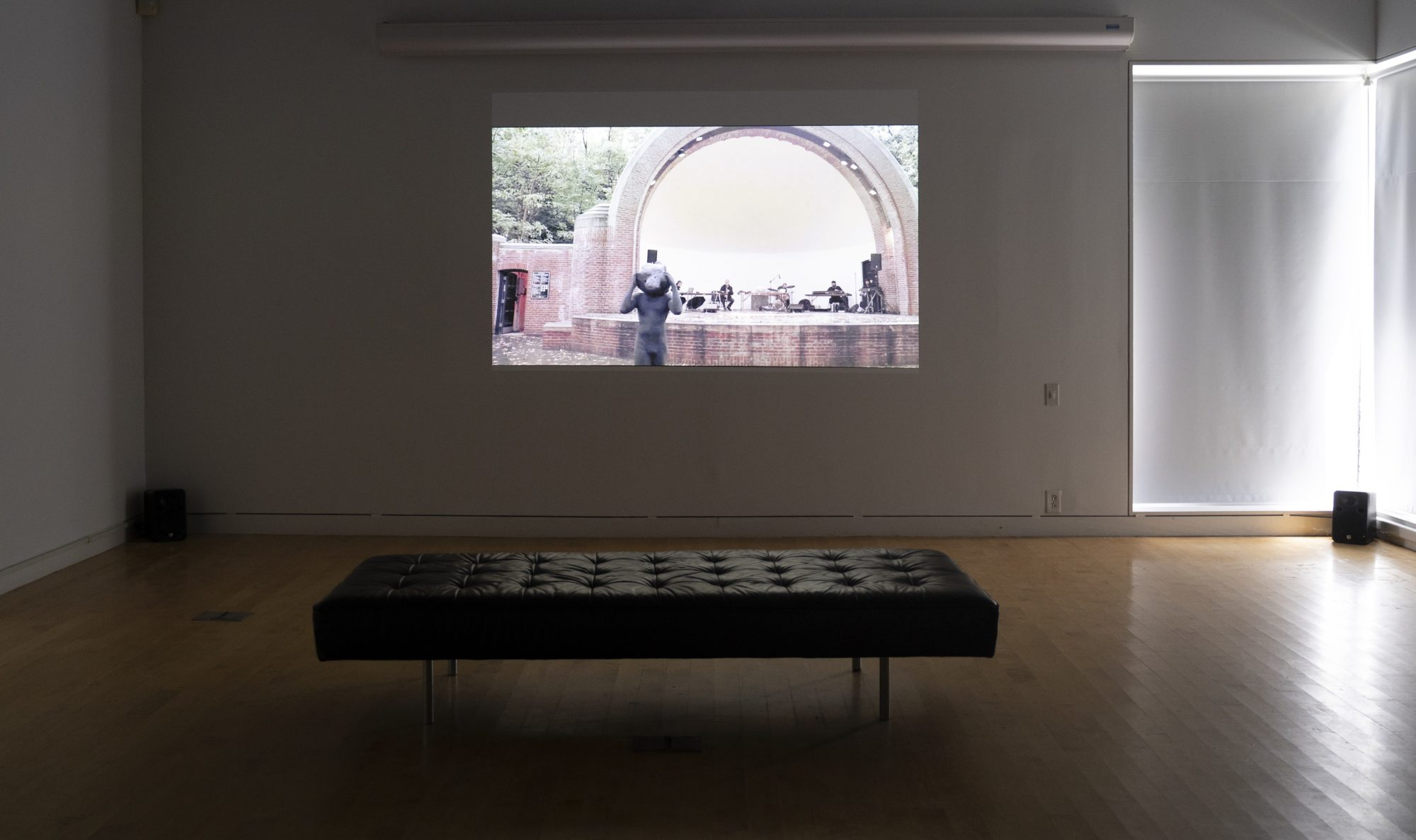 Projection of performance video on wall with black bench in front.
