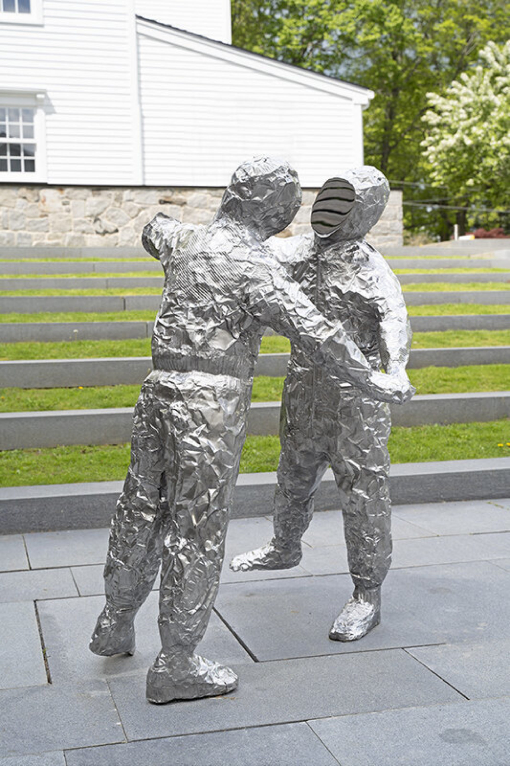 Two figures made out of crumpled baking pans cast in polished stainless steel