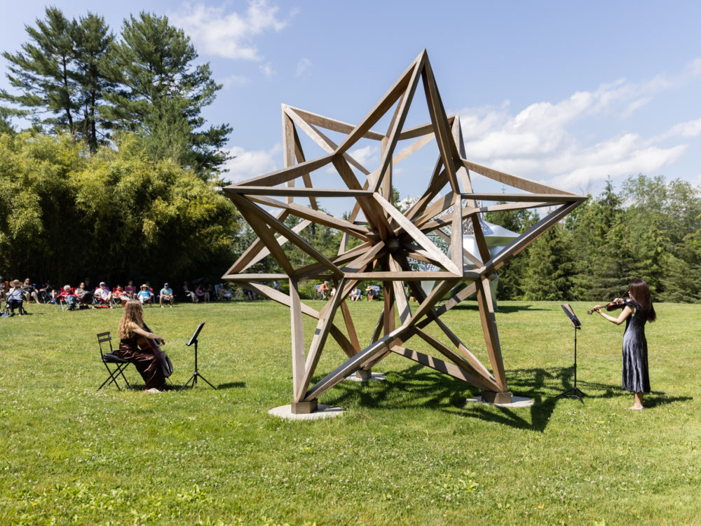 Two musicians perform in front of a large wooden star sculpture