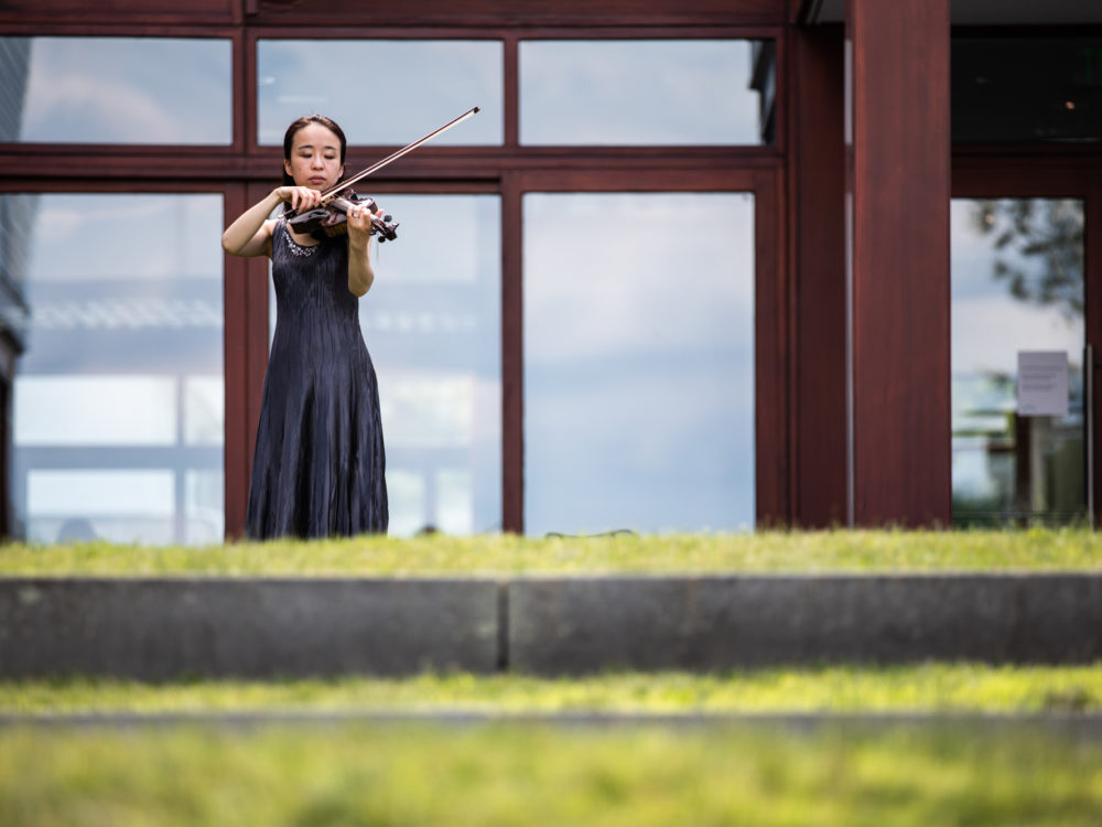 A violinist performs with large windows in the background