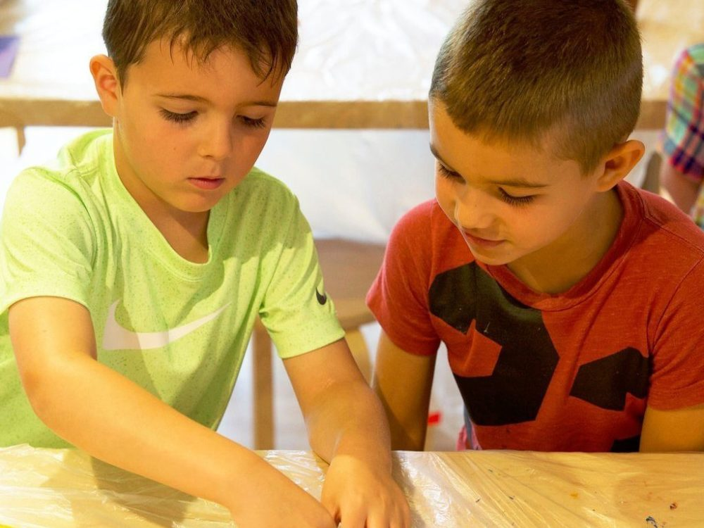 Two young children work on an art project
