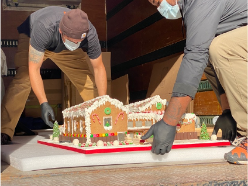 Two art handlers configure Caitlin's gingerbread house in a moving truck