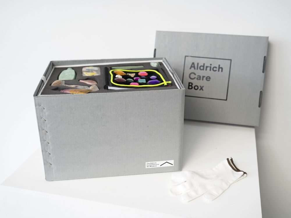 Open gray archival box with the artwork contents of small sculptures and an artists' book in foam. The box lid and white gloves are nearby.