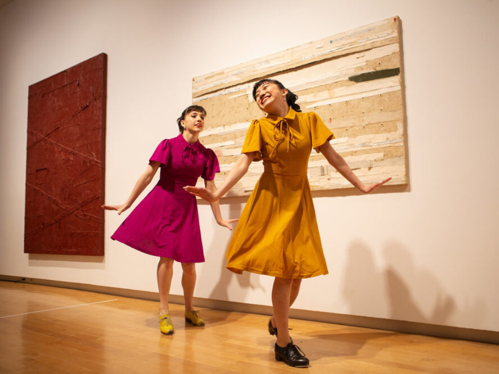 Two dancers in colorful dresses dancing in the gallery