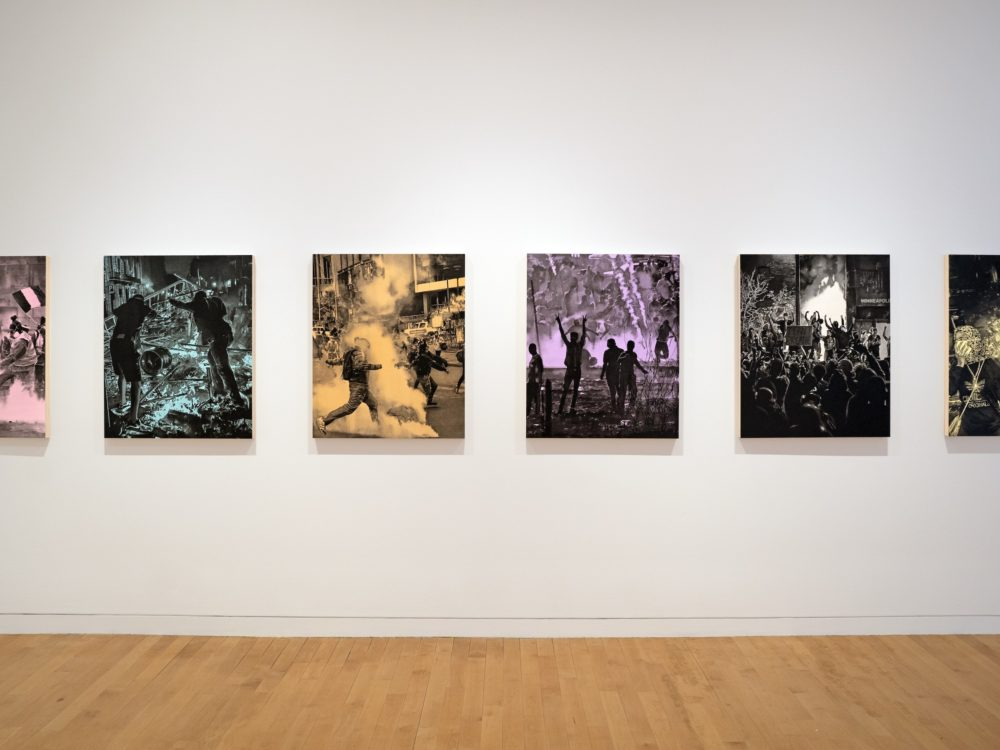 Six single color and black paintings of protest scenes hung in a line on a white wall.