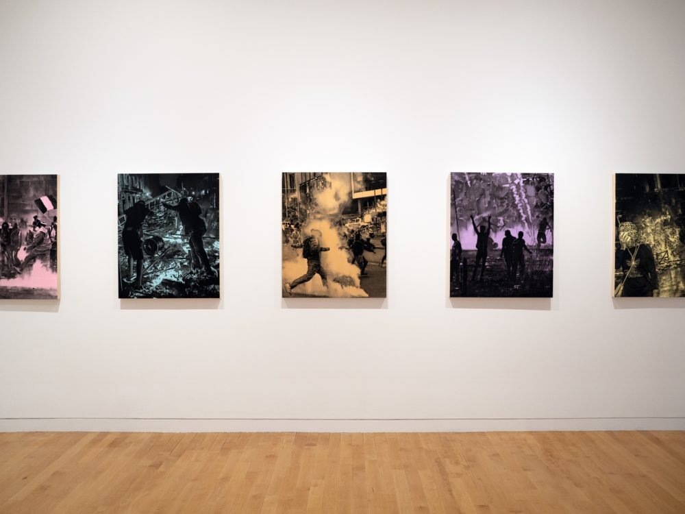 White wall with five black and single color drawings of protests.