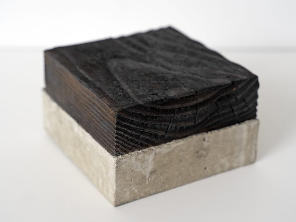 A small square of concrete with a square of the same size of burnt wood attached.