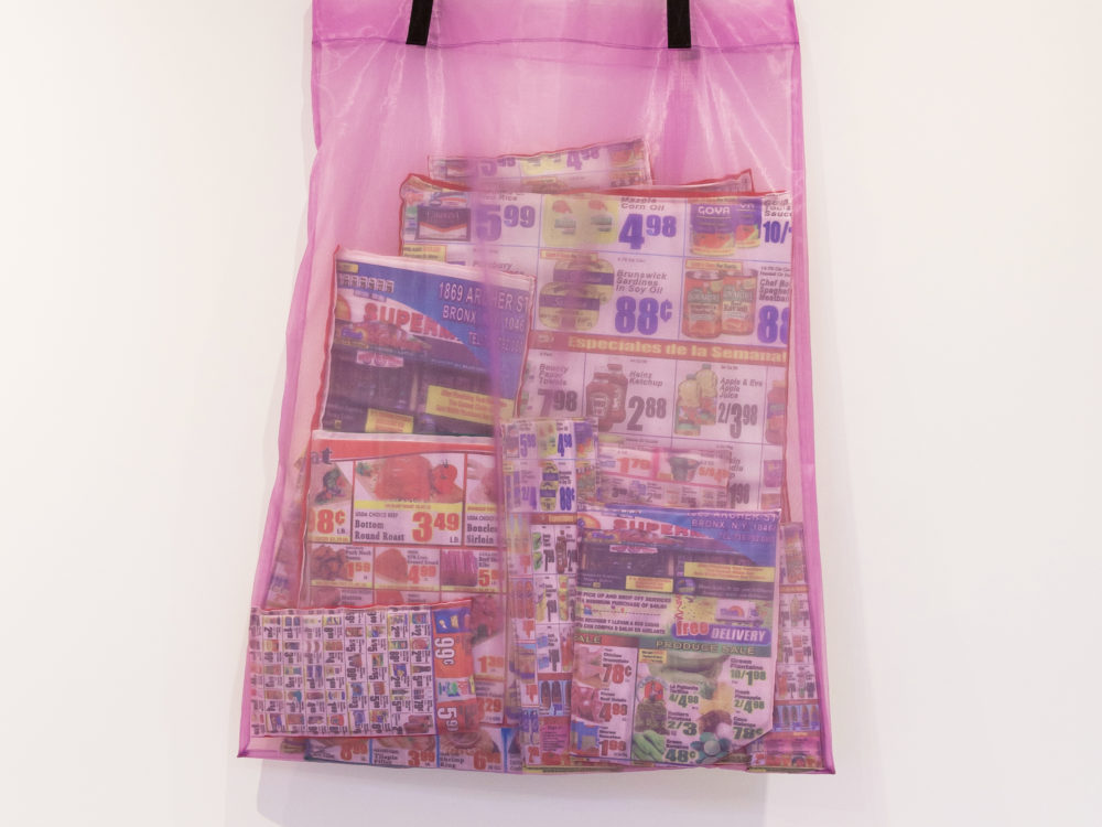 Large pink mesh bag hanging from a white wall