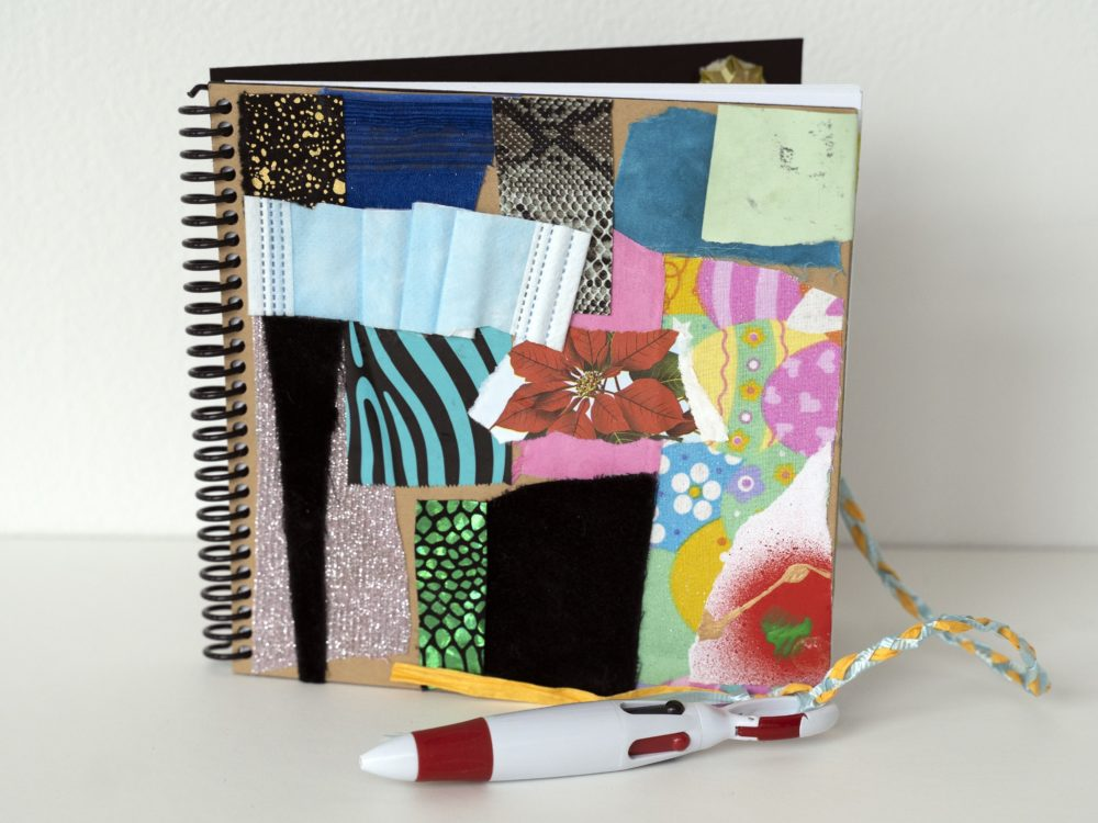 Image of an upright spiral bound notebook with collaged elements on the cover including a piece of a disposable face mask and shiny fabrics. A pen is attached.