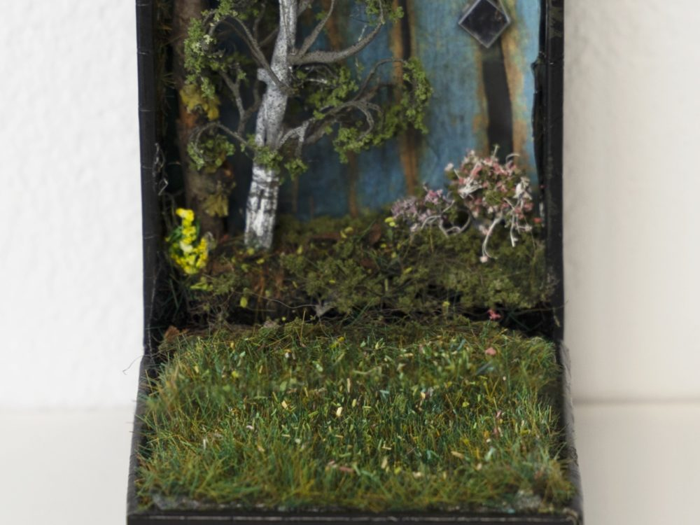 Open small jewelry box with a landscape diorama inside including grass and trees.