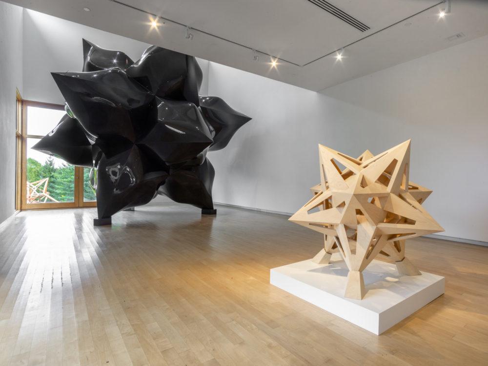 Smaller wooden star sculpture in foreground, large-scale black star sculpture in background.