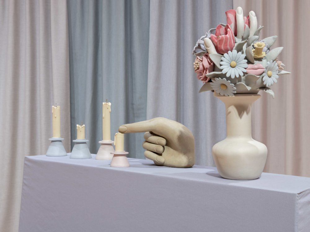 Clay sculptures of extinguished candles with a surrealist bouquet with pastel-colored curtains in the background.