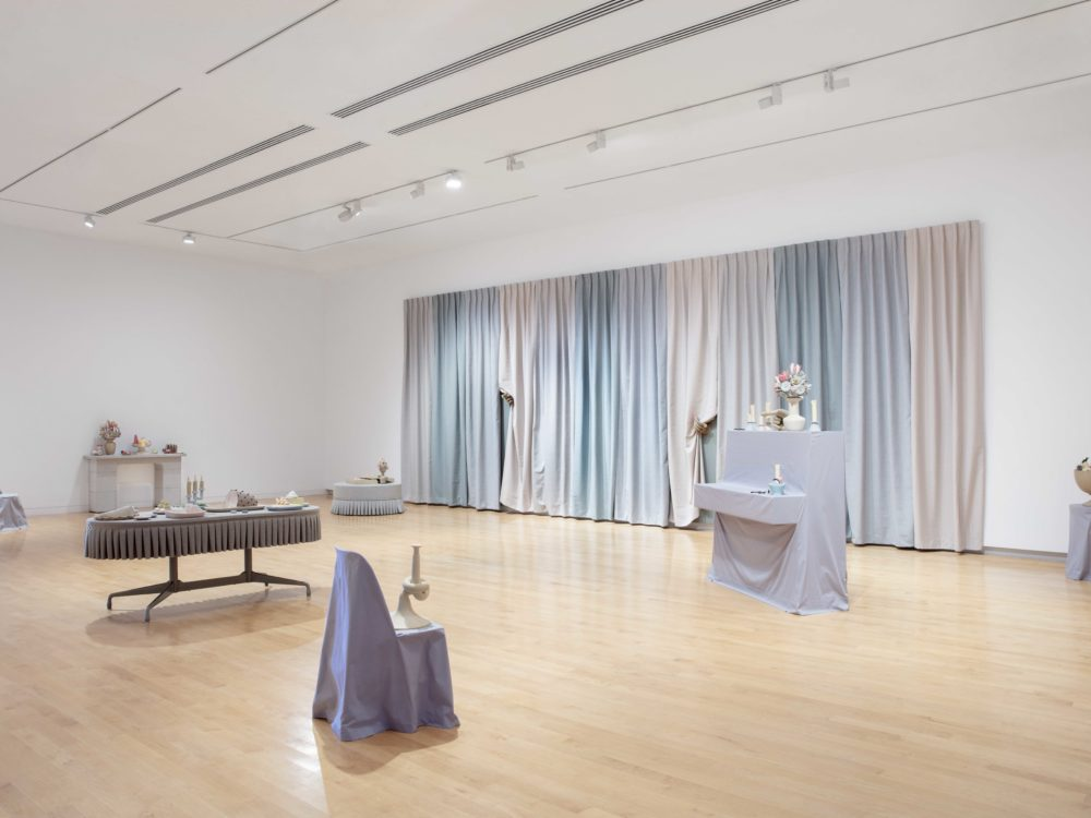 Overall installation view with gray slipcovered furnishings with surrealist clay objects and a large-scale multi-colored curtain on the back wall.