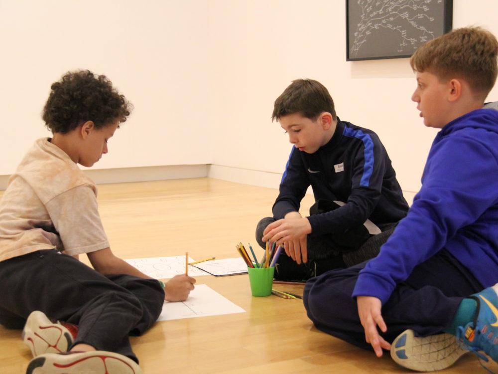 Three children work on art projects