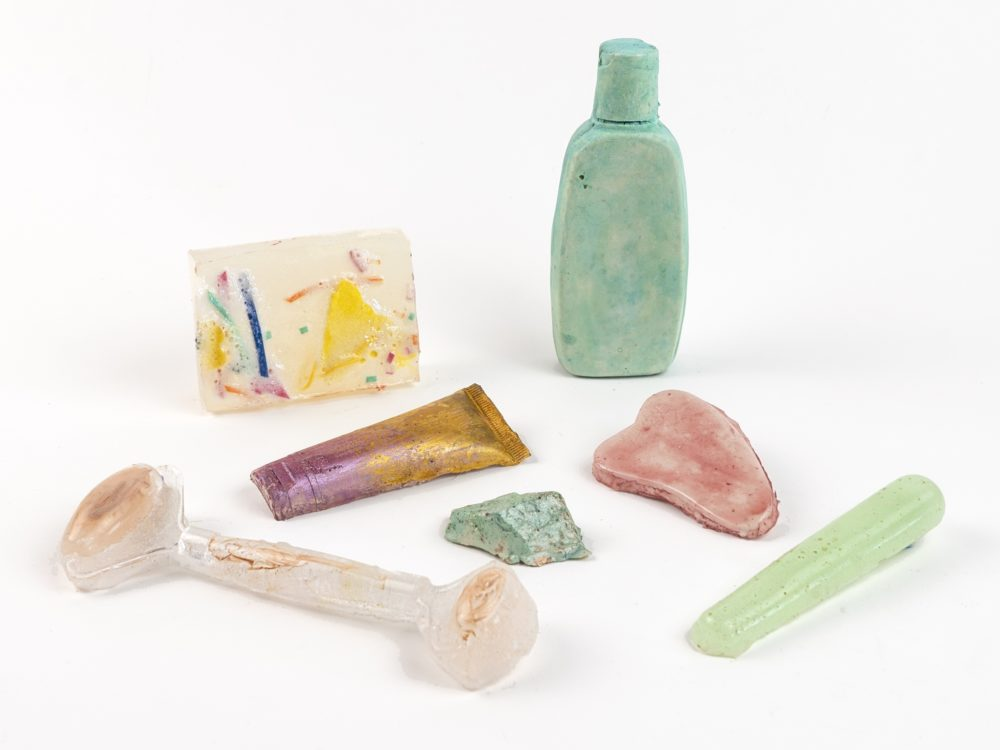 Cast sculpture colored objects related to self-care practices including a bar of soap, facial roller, gua sha stone, and tube and bottle of lotion.