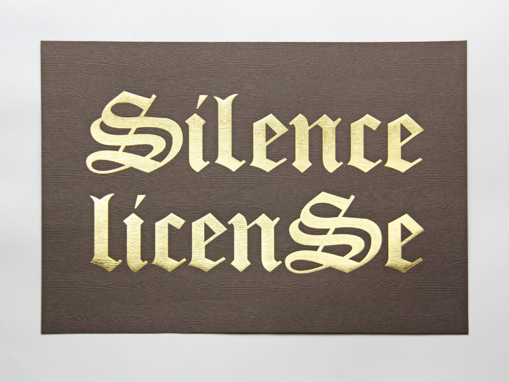 "A print with ""Silence License"" written in gold lettering on brown wood grain paper background."