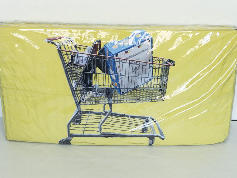 Clear plastic wrapped rectangular yellow mattress with an image of a shopping cart with assorted items inside.
