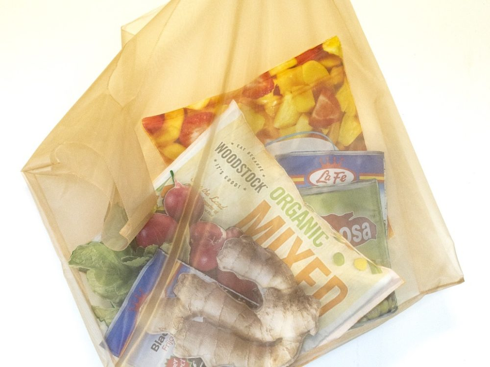 Large golden mesh bag hung on a white wall containing objects such as a ginger root, bag of fruit, frozen vegetables, and radishes.