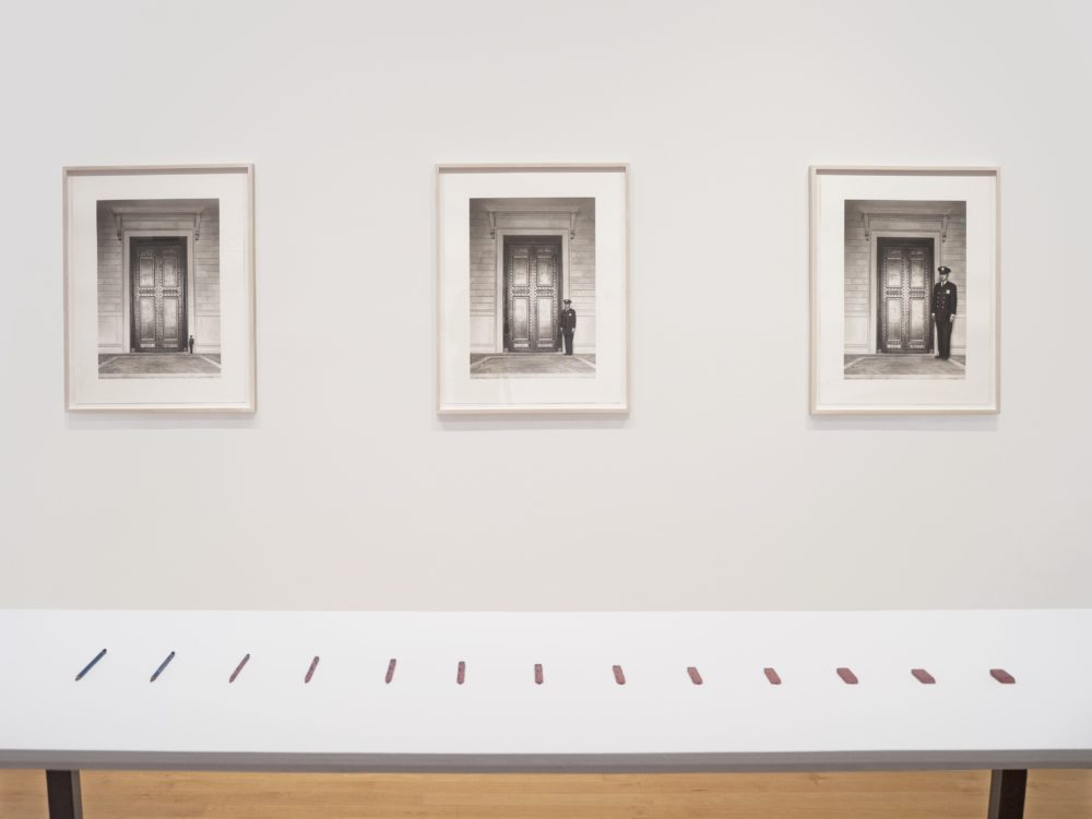 Installation view with a table in the foreground with small sculptures of a pencil turning into an eraser; on the wall behind are three framed drawings.