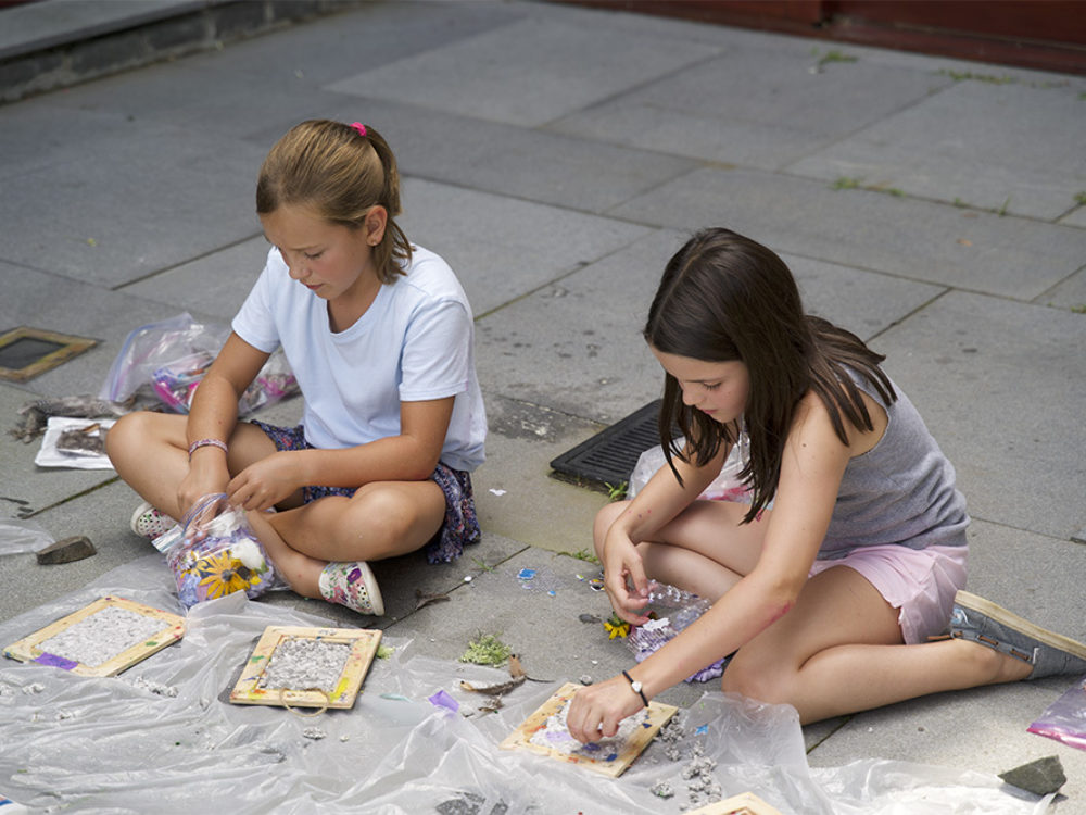 Two children work on art projects
