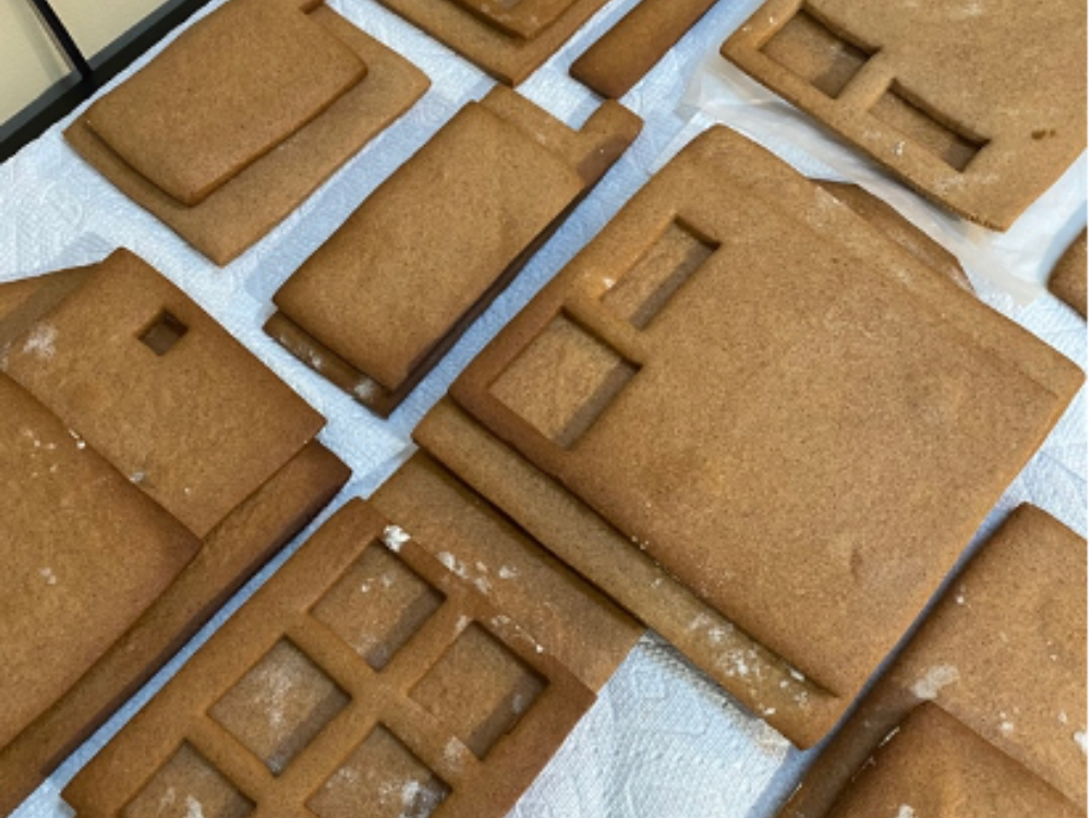 Gingerbread house pieces with window cutouts against a white background