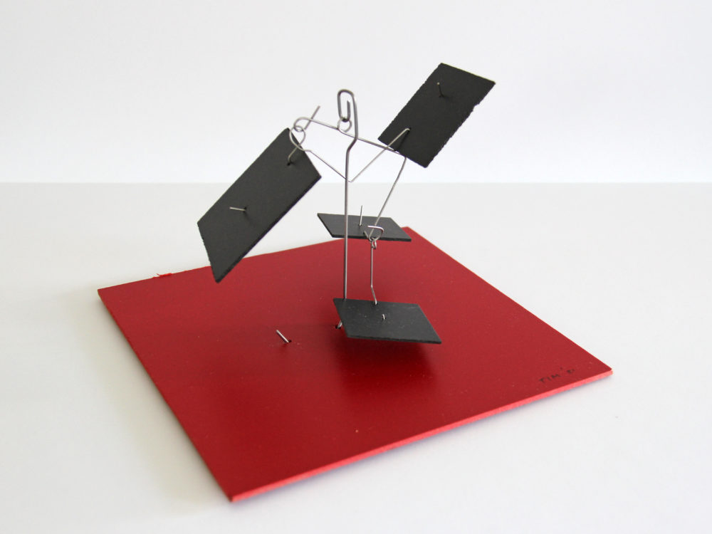 Sculpture with square red base, metal armature, and black rectangular elements.