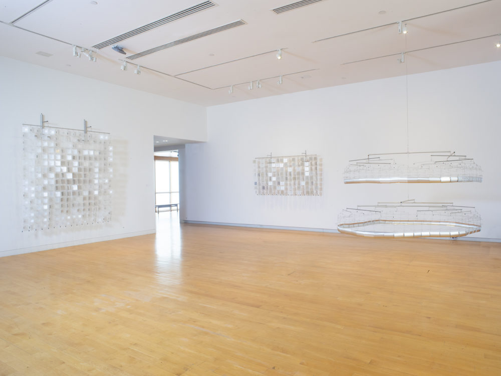 Gallery space with three sculptures made of reflective material and wire, two are hung on the wall and one is suspended from the ceiling.