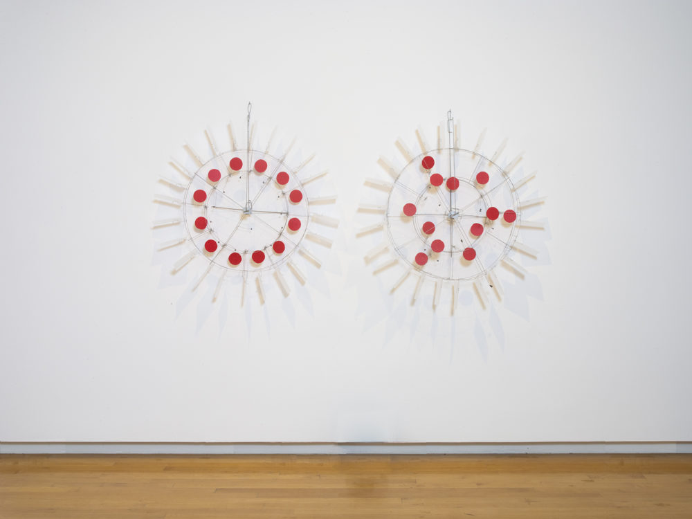 Two circular sculptures hung on a wall with red dots in the middle and reflective material outer pieces connected by wire.
