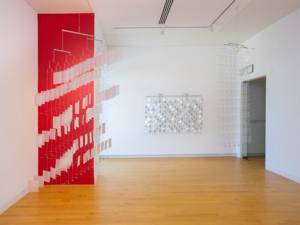 Gallery with one wall painted red and three suspended reflective material and wire sculptures.
