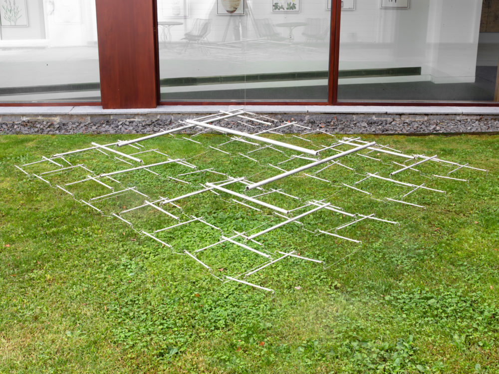 Open square silvery kinetic sculpture installed low to the grass.