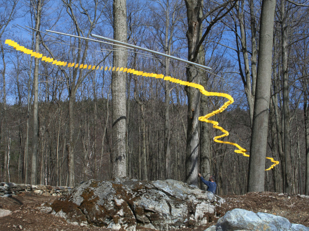 Multi-part suspended sculpture of yellow squares strung together forming a curving line through a winter forest canopy.