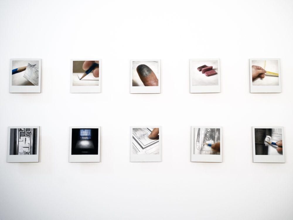 Grid of paintings on Polaroid photographs showing elements of the drawing process, for example pencils, erasers, fingers.