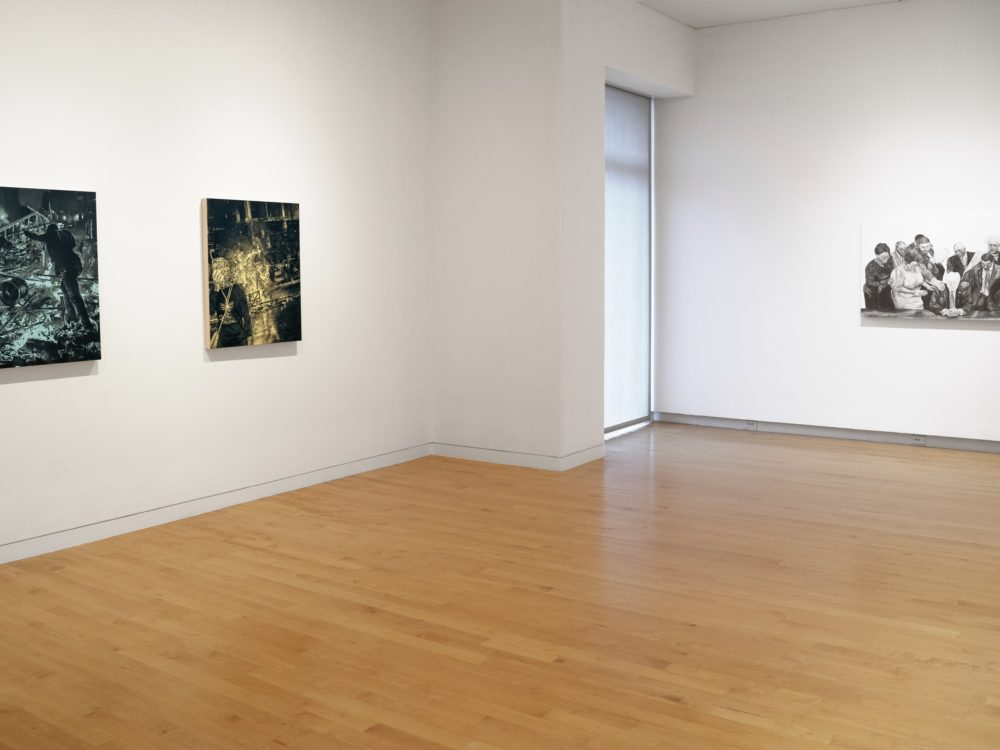 Installation view of gallery with two paintings of protest scenes with black images on single colored backgrounds at left and a black and white drawing at right